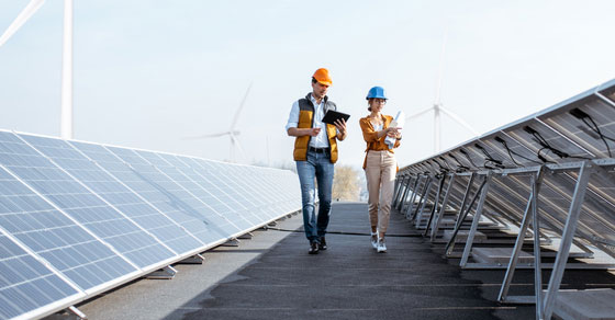 Two workers inspecting solar panels