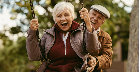 An elderly couple playing on a swing set