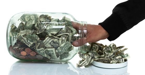 a hand in a money jar