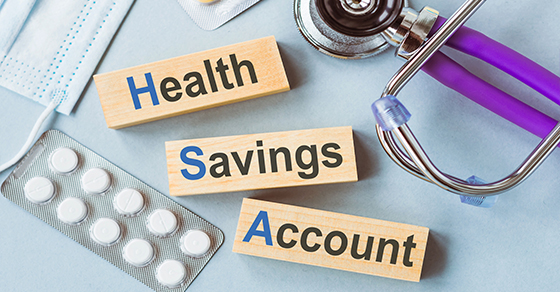 stethoscope, face mask, pills, blocks spelling out health savings account